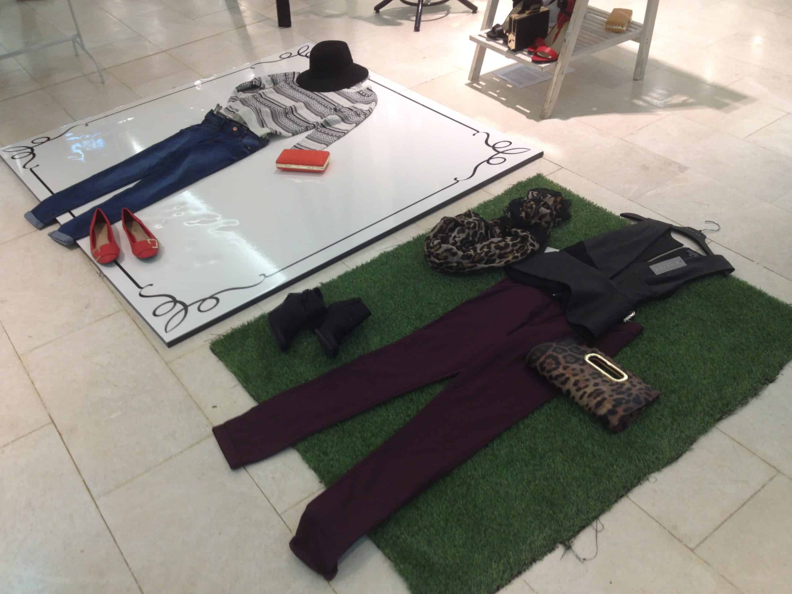 Outfits are laid out on the floor of a clothing store.