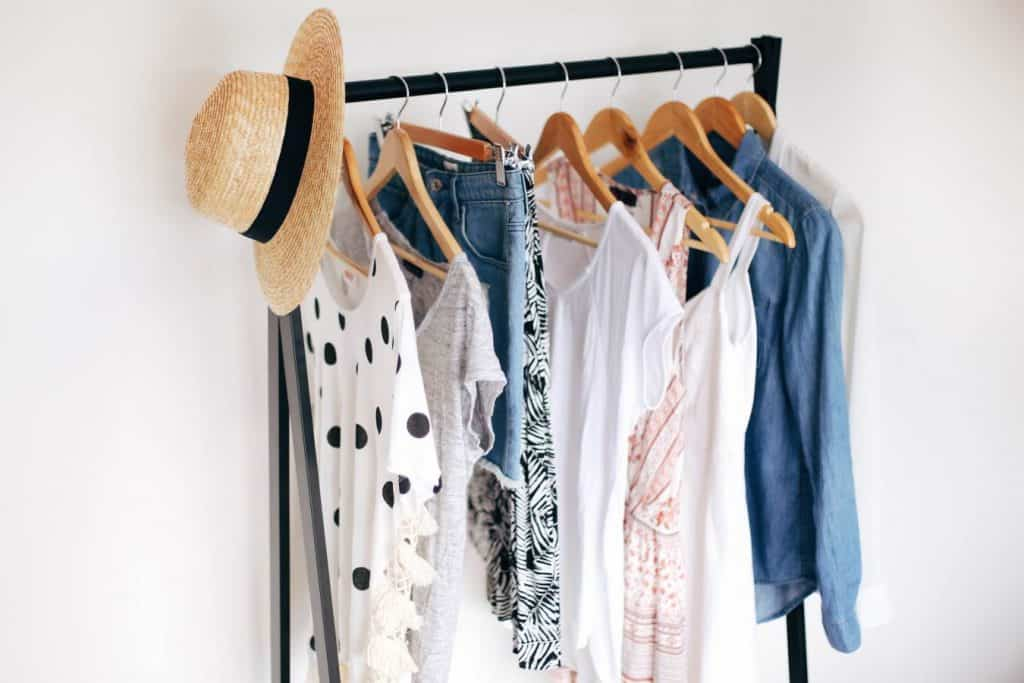 Clothing rack hanging shirts, jeans, dresses and a hat.
