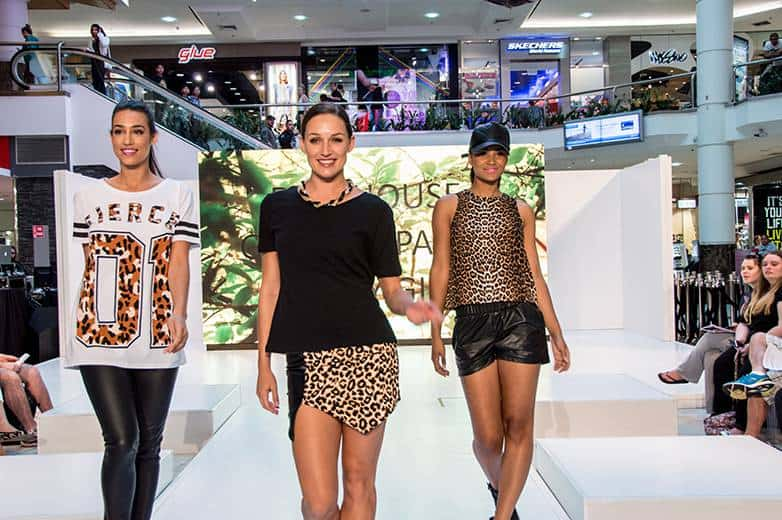 Models walking runway for a fashion event.