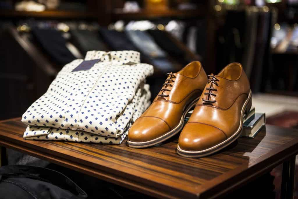 Men's folded shirt and shoes are on display.