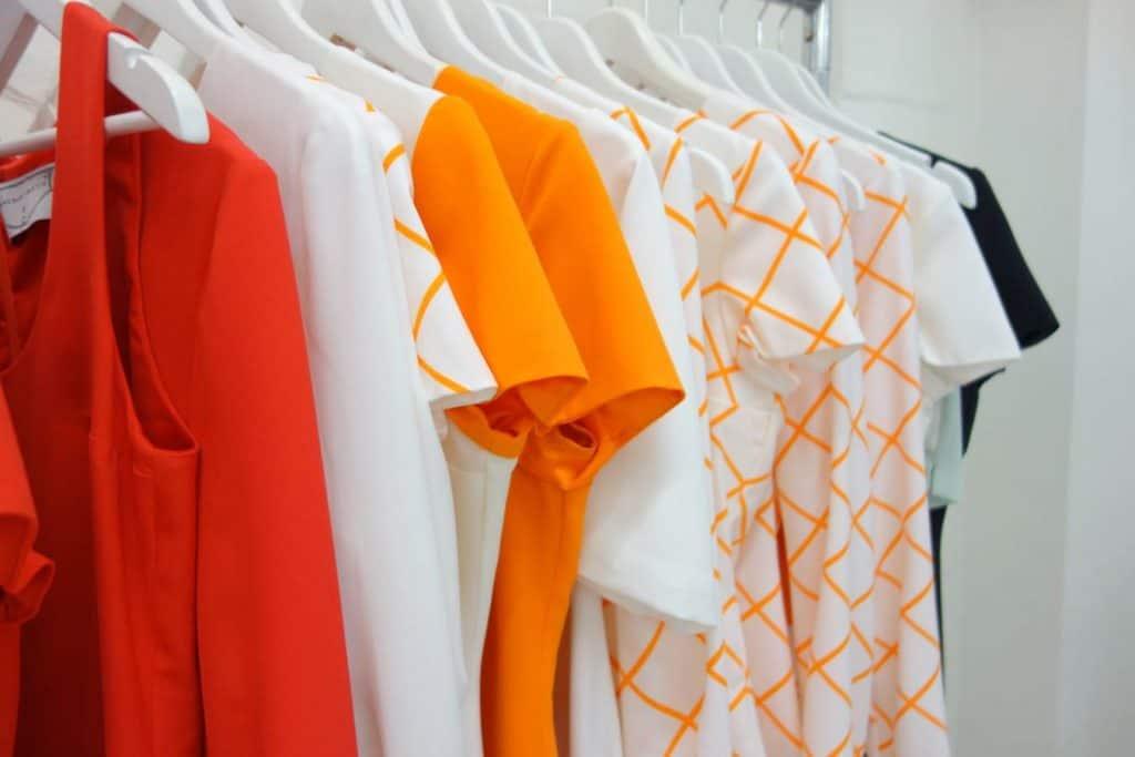 Clothing rack holding orange clothes.
