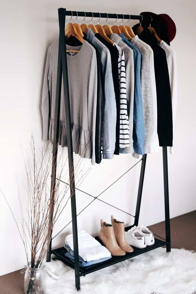 Clothes rack holds multiple sweaters, shoes, jeans and a hat.