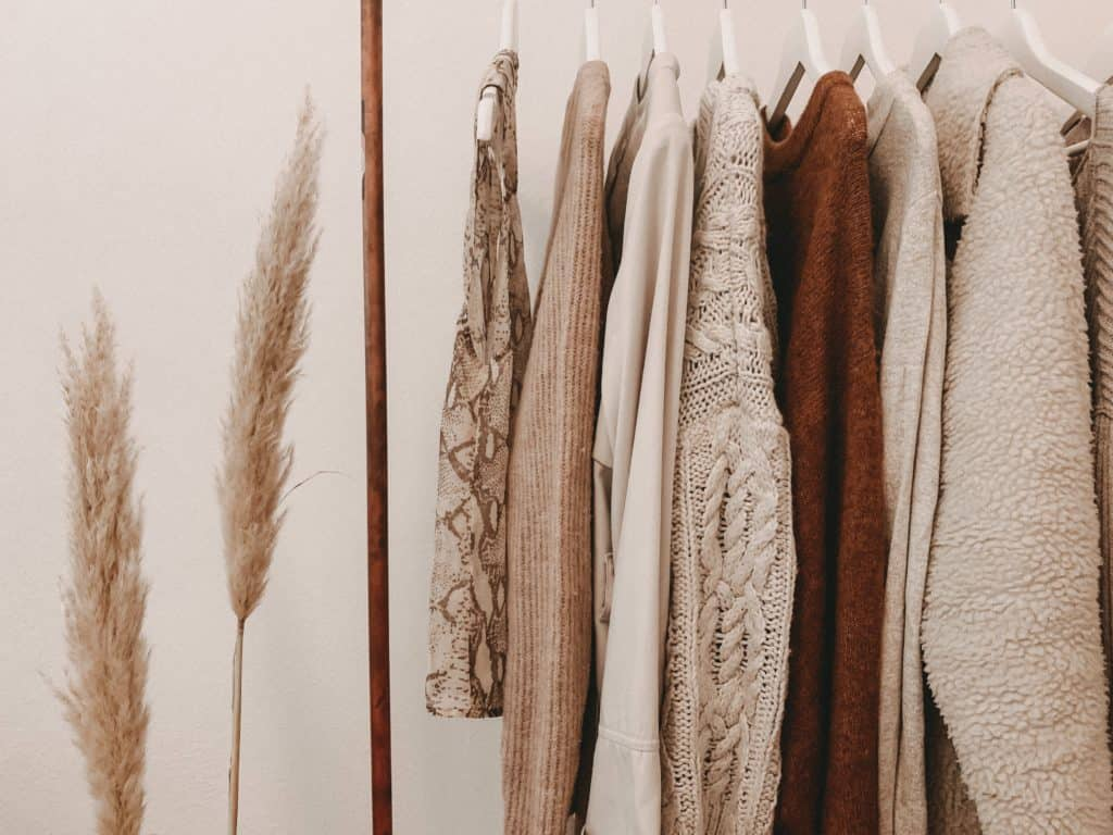 Clothing rack holds beige Hayley Cooper styling pieces.
