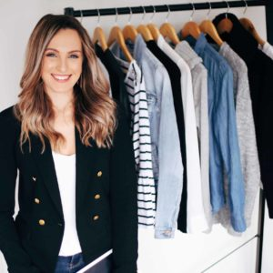 Hayley Cooper poses and smiles in front of clothes rack.