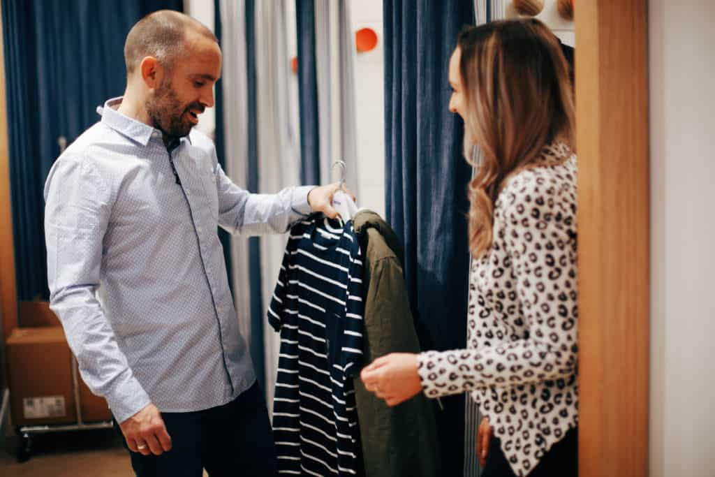 Hayley Cooper inspects clothes in a changing room with a male client.