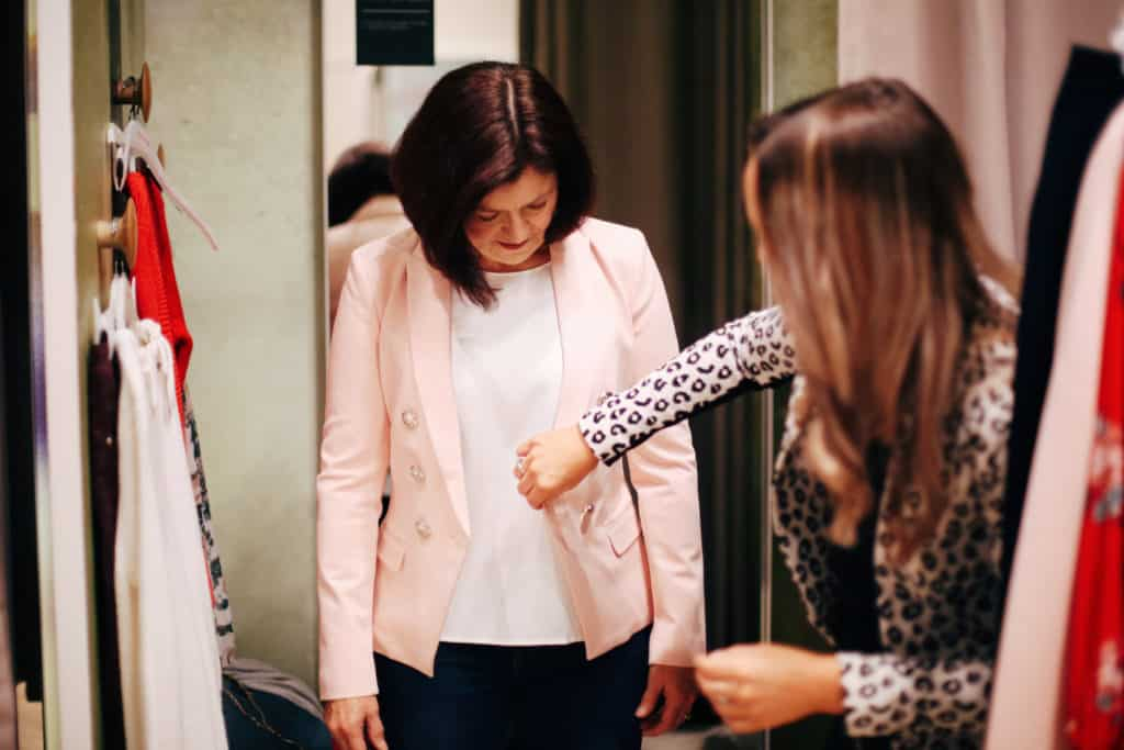 Hayley Cooper adjusts a pink blazer on a client.