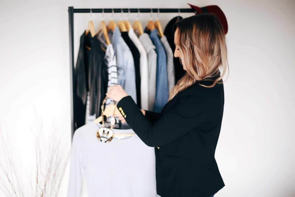 Hayley Cooper hangs clothes on rack.