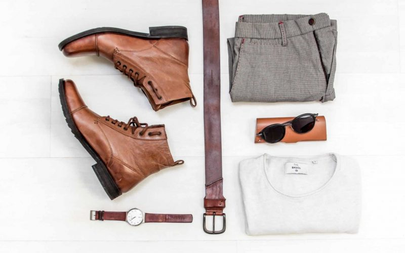 Birdseye view of clothing, boots, a watch, a belt, glasses and a purse.