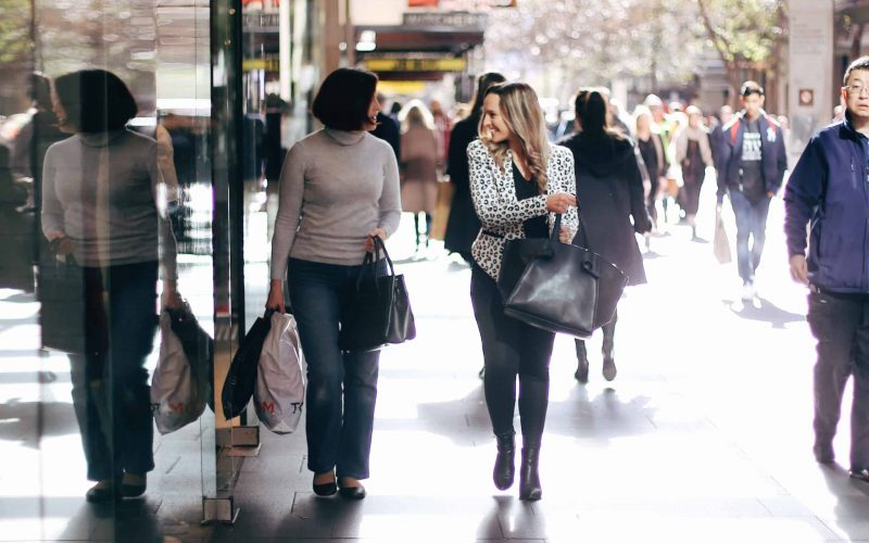 Hayley Cooper walks down the street with a client, smiling and carrying a bag.