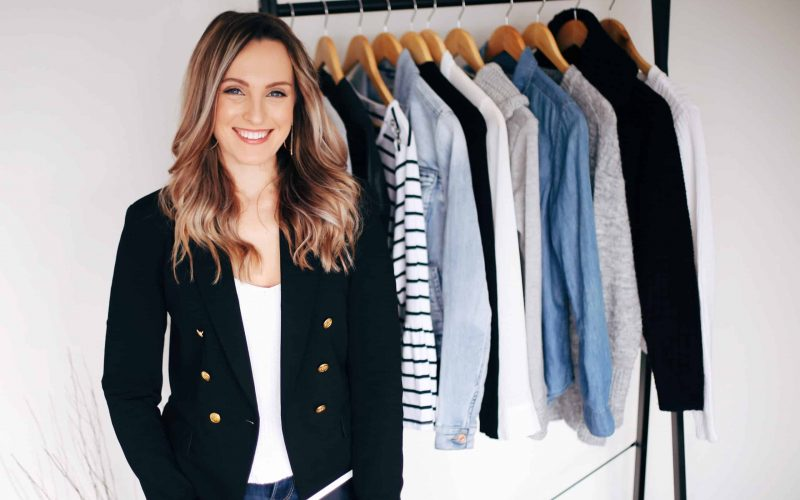 Hayley Cooper poses and smiles in front of a clothing rack.