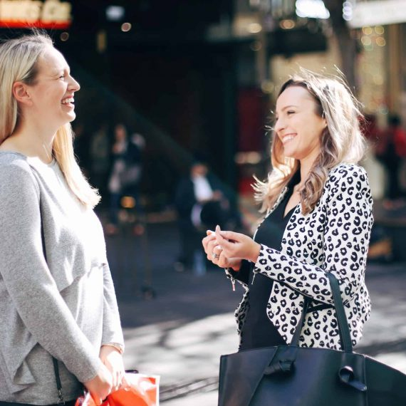 Hayley Cooper laughs with a client on the street.