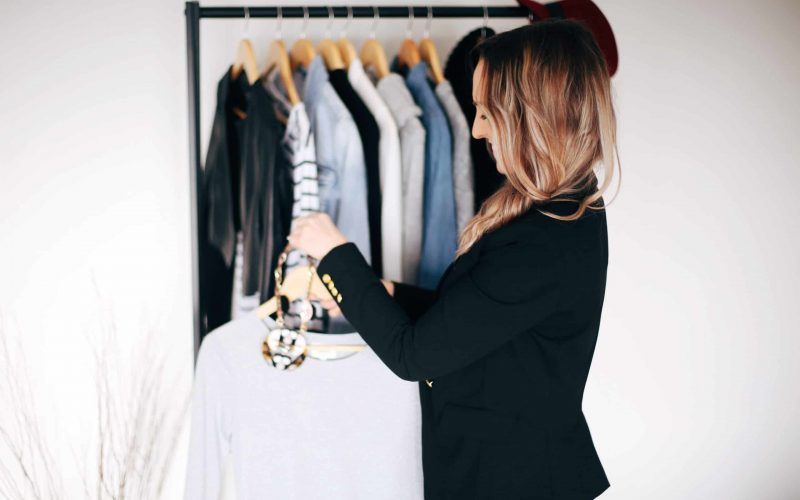 Hayley Cooper hangs clothing on rack.